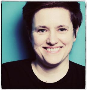 Lachende Frau vor türkiser Wand Petra Coddington Fotografin